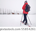 Woman snowshoeing in snow fall. Dark grey clouds 55854261
