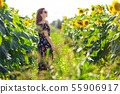 Happy woman in a field of sunflowers 55906917