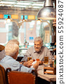 Cheerful pensioners playing cards in the pub together 55924087