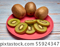 view of a pink plate with slices of kiwi and whole 55924347