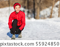Winter running woman getting ready to run in snow 55924850