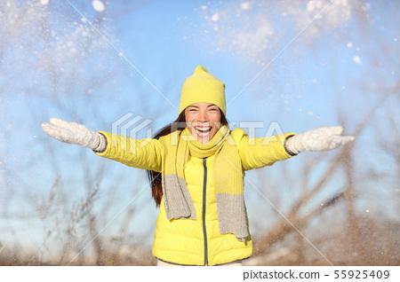 Winter fun girl throwing snow playing outside 55925409