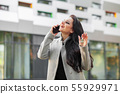 Portrait of a young woman realtor or businesswoman standing outdoors on the modern residential 55929971