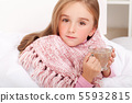 Child girl with a cup of hot tea in bed 55932815