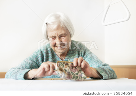 Cheerful elderly 96 years old woman sitting at table at home happy with her pension savings in her 55934054