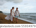Young couple in love walks on the beach at sunset 55934979
