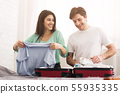 Happy couple preparing for honeymoon, folding clothes 55935335