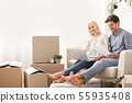 Couple reading certificate of property sitting with laptop on couch 55935408