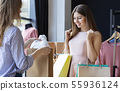 Salesgirl showing happy customer her gift for purchases 55936124