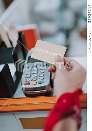 Hand of man holding gold card and paying 55938216