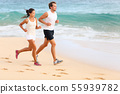 Running couple jogging on beach exercising sport 55939782