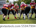 Full-length photo of sportswomen playing american football on green lawn 55947994