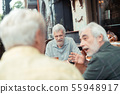 Retired men talking and drinking alcohol outside 55948917