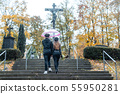 Man and woman walking up steps on cemetery towards a cross 55950281