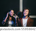 Two young singers performing song in record studio.Professional musicians 55956642