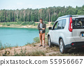 man near white suv car at the edge looking at lake with blue water 55956667