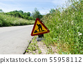 Roadwork sign by roadside among green grass 55958112