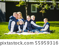 Big Family Relaxing In Green Nature. Happy family portrait on outdoor, group six people sit on grass 55959316