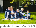 Big Family Relaxing In Green Nature. Happy family portrait on outdoor, group six people sit on grass 55959324