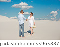 Young couple enjoying the sunset in the dunes. Romantic traveler walks in the desert. Adventure 55965887