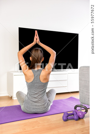Home fitness woman doing yoga exercise watching tv 55977672
