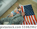 Military servant lying on the floor near his cute lovely daughter 55982962