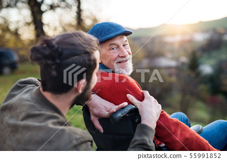 Senior father with wheelchair and his son on walk in nature, talking. 55991852