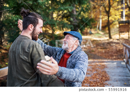Senior father and his son on walk in nature, hugging and talking. 55991916