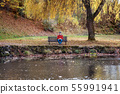 Lonely senior man sitting on bench by lake in nature, looking at camera. 55991941