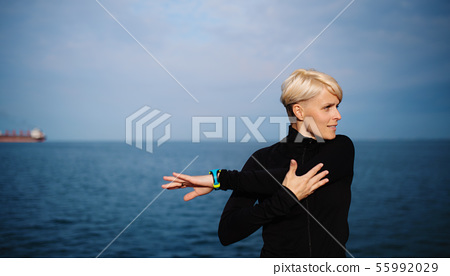 Front view portrait of young sportswoman sitting outdoors on beach, stretching. 55992029