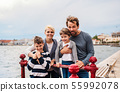 Portrait of young family with two small children outdoors on beach. 55992078