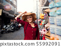 Young woman standing outdoors in town on holiday, trying on a hat. 55992091