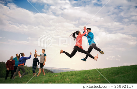 Large group of fit and active people jumping after doing exercise in nature. 55992117