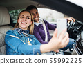 Happy young couple with smartphone sitting in car, taking selfie. 55992225