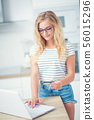 Young blonde woman holding credit card and using 56015296