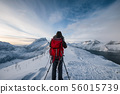 Mountaineer with backpack taking a photo a scenery 56015739