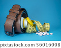 Conceptual image with pills, belt and tape measure 56016008