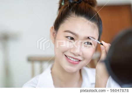 woman brunette cosmetics using brow brush 56047878