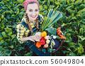 Farmer woman in a field offering organic vegetables 56049804