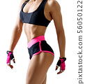 Unrecognizable athletic woman in sportswear demonstrated her muscular body. 56050122