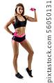 Young woman in sportswear demonstrate her beautiful muscular body. 56050131