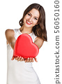 Young woman in white dress holds heart shaped box. 56050160
