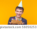 Positive funny young asian guy with a cap and a burning candle and a homemade cake in his hands 56050253