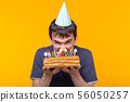 Portrait of a funny positive guy with a paper cap and glasses holding a congratulatory homemade cake 56050257