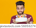 Close-up young handsome man blows off a candle from a burning cake posing for a yellow background 56050274