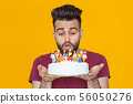 Close-up young handsome man blows off a candle from a burning cake posing for a yellow background 56050276