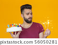 Positive young man holding a happy birthday cake and two burning bengal lights posing on a yellow 56050281