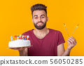 Positive young man holding a happy birthday cake and two burning bengal lights posing on a yellow 56050285