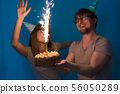 Funny nerd man and woman are wearing holidays caps and glasses holding birthday cake with sparkler 56050289
