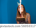 Cheerful young blurred girl student in glasses holding a congratulatory cake with a candle standing 56050317